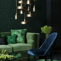 12-a-moody-space-with-a-green-velvet-sofa-and-pillows-and-a-navy-velvet-chair-and-brass-lamps